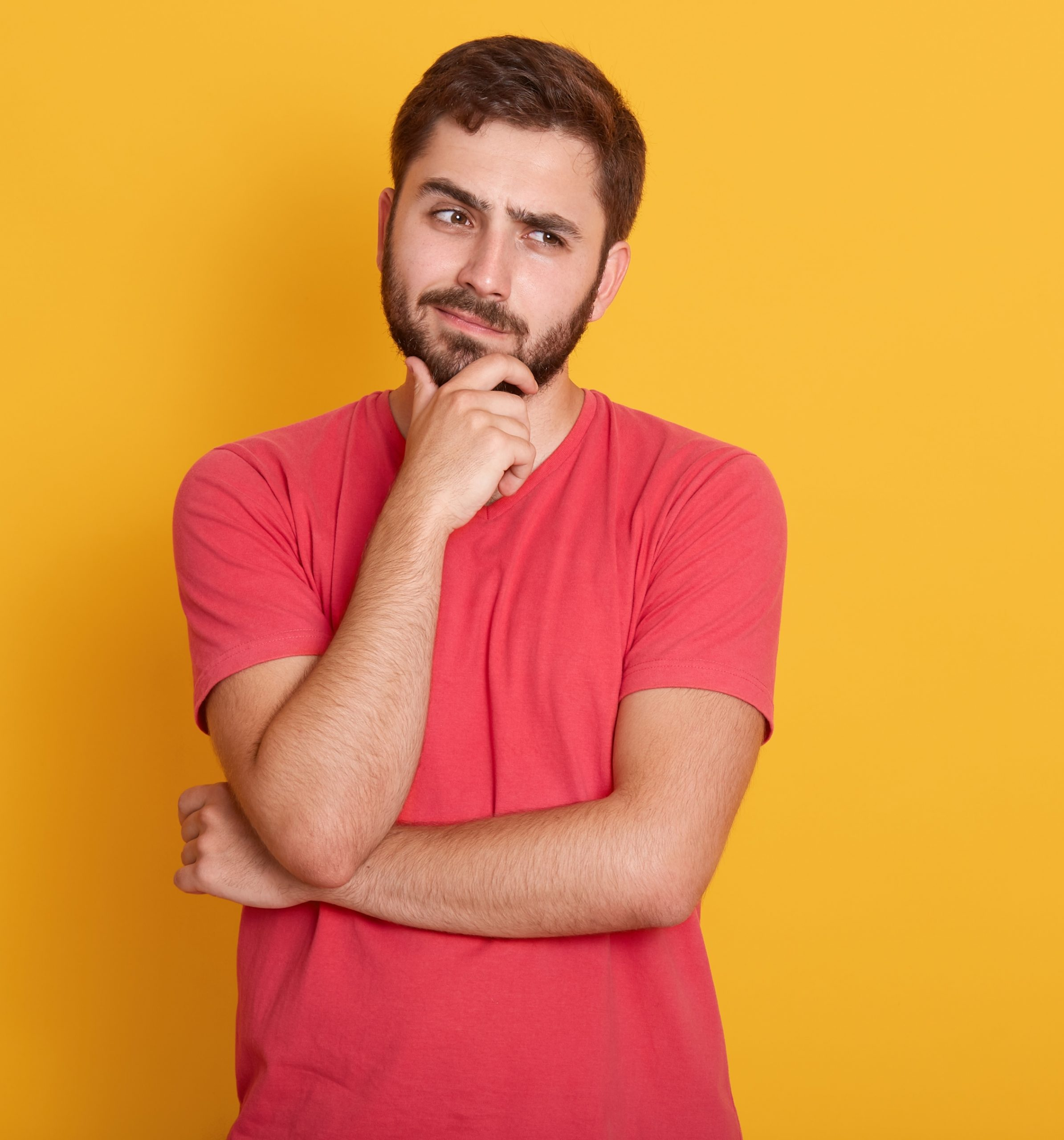 Horizontal shot of serious unshaven male dresses casual red t shirt, keeps hand under chin, looks aside with serious facial expression, thinks about something, poses over yellow wall with free space.